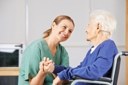 caregiver holding hands with senior women in a wheelchair
